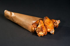 Chicken buffalo. Fried buffalo wings in a paper bag on a black background Royalty Free Stock Photos
