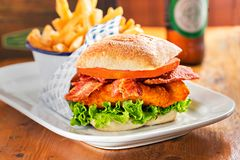 Chicken burger with bacon and lettuce. Fries and beer in restaurant stock images
