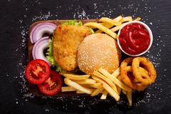Chicken burger with french fries and onion rings, top view. Chicken burger with french fries and onion rings on wooden board, top view Royalty Free Stock Photo