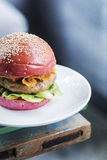 Chicken burger with gherkins beetroot bread bun Royalty Free Stock Image