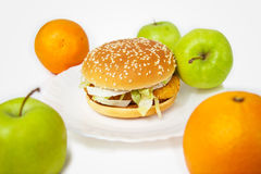 Chicken burger next to many apples and oranges Stock Photos
