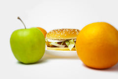 Chicken burger next to orange and an apple Stock Image