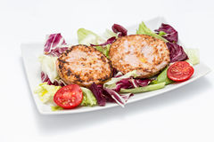 Chicken burger over salad. Chicken burgers over salad - Two burgers, chicory, lettuce and tomato Royalty Free Stock Images
