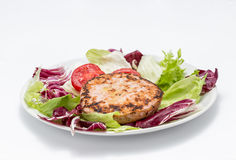 Chicken burger over salad. Two burgers, chicory, lettuce and tomato Royalty Free Stock Images