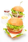Chicken burger with vegetables, cheese and sauces on board Royalty Free Stock Photo