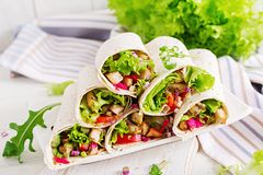Chicken burrito. Healthy lunch. Mexican street food fajita tortilla wraps. With grilled chicken fillet and fresh vegetables royalty free stock images