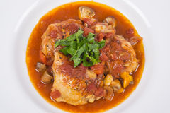 Chicken Cacciatore #1. Chicken cooked in tomato based sauce with red bell peppers and mushrooms, garnished with Italian flat leaf parsley #1 royalty free stock image