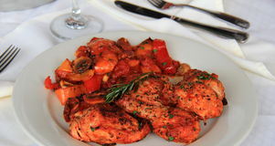 Chicken cacciatore with tender sweet peppers on white plate at restaurant royalty free stock images