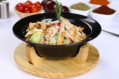 Chicken Caesar Salad. On the black bowl Royalty Free Stock Photography