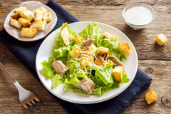 Chicken caesar salad. With cheese and croutons over rustic wooden background Stock Photography