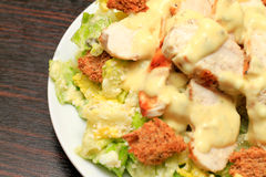Chicken caesar salad. In a white Dish on a wood table Royalty Free Stock Image