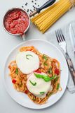 Chicken caprese with tomato and mozzarella cheese, served with linguine, tomato sauce and basil, vertical, top view, closeup. Chicken caprese with tomato and stock photography