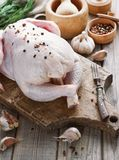 Chicken carcass on a wooden background with spices, cooking in the kitchen, rustic style.  Stock Image