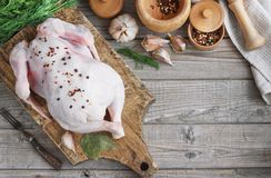 Chicken carcass on a wooden background with spices, cooking in the kitchen, rustic style.  Royalty Free Stock Photography