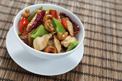 Chicken cashew nuts. Chicken with cashew nuts, chili, peas, capsicum on white background Stock Photo
