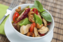 Chicken cashew nuts. Chicken with cashew nuts, chili, peas, capsicum on a bamboo mat with fork Royalty Free Stock Images