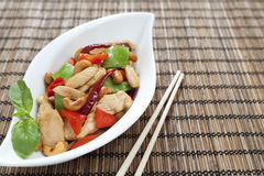 Chicken cashew nuts. Chicken with cashew nuts, chili, capsicum and snow peas on a bamboo mat with chop sticks Stock Photo