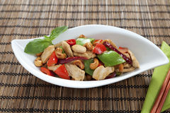 Chicken cashew nuts horizontal. Chicken with cashew nuts, chili, capsicum and snow peas on a bamboo mat with chop sticks Royalty Free Stock Images