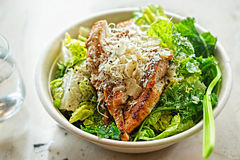 Chicken Ceasar salad. Cos lettuce leaves, grilled chicken breast sliced, parmesan cheese. Restaurant table.  royalty free stock photos