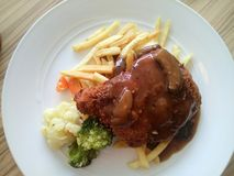 Chicken chop brown mushroom sauce french fries restaurant menu. An image of a common chicken chop dish with brown mushroom sauce and fries. Garnesh with Royalty Free Stock Photography