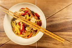 Chicken chow mein and chopsticks on wooden table stock photography
