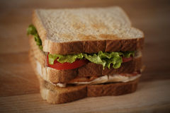 Chicken club sandwich. On a wooden cutting board with very shallow depth of field royalty free stock image