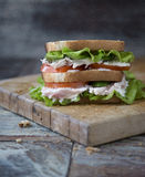 Chicken Club Sandwich with Lettuce and Tomato. On old wooden table royalty free stock photo