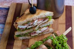 Chicken club sandwich. Tasty chicken club sandwich with fries on wooden table royalty free stock photo
