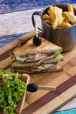 Chicken club sandwich. Tasty chicken club sandwich with fries on wooden table stock photos