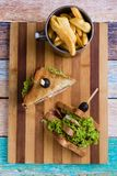 Chicken club sandwich. Tasty chicken club sandwich with fries on wooden table stock image