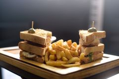 Chicken club sandwich on a white plate with spicy french fries. Club Sandwich with Cheese, PIckled Cucmber, Tomato and Smoked Meat. Garnished with French Fries royalty free stock photo