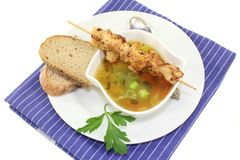 Chicken consomme. A bowl of chicken consomme and a chicken skewer Royalty Free Stock Image