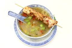 Chicken consomme. A bowl of chicken consomme and a chicken skewer Stock Photos