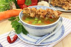 Chicken consomme. A bowl of chicken consomme and a chicken skewer Stock Photo
