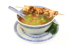 Chicken consomme. A bowl of chicken consomme and a chicken skewer Royalty Free Stock Photography