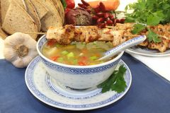 Chicken consomme. A bowl of chicken consomme and a chicken skewer Royalty Free Stock Photos