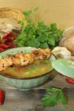 Chicken consomme with chicken skewers and vegetables. Chicken consomme with chicken skewers, vegetable and greens Stock Images