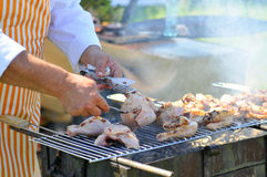 Chicken cooking on barbecue grill. Chicken cooking on outdoors barbecue grill Royalty Free Stock Photo