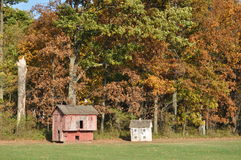 Chicken coop in fall foilage. Red and white old animal houses in a serene fall foilage background Stock Photography