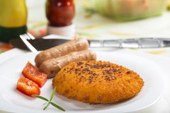 Chicken cordon Bleu on plate with two sausages Stock Photography