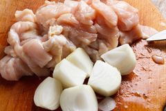Chicken cubes and onion on the kitchen cutting board Royalty Free Stock Photography