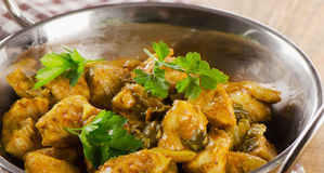 Chicken curry in a balti dish on wooden table.