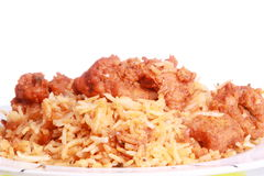 Chicken curry over chicken biryani. Spicy boneless chicken curry is served over chicken biryani and photographed against white background Royalty Free Stock Photography