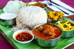 Chicken curry thali served with dry potato and caulifower curry rasam curd and papad Stock Photos