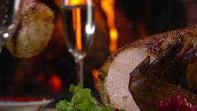 Chicken cut with knife on background of fireplace