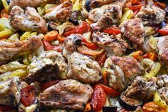 Chicken, cut into pieces, baked with vegetables in the oven Stock Image