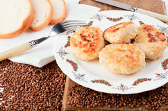 Chicken cutlet and buckwheat. Four chicken cutlets on a white plate. plate is on a wooden cutting board. Near sprinkled buckwheat. bread on a white napkin Stock Photo