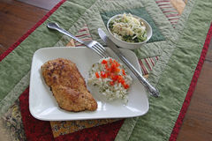 Chicken Cutlet dinner. With buttered rice and red pepper garnish and broccoli salad Stock Image
