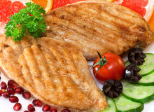 Chicken cutlets. With a cucumber and a grapefruit on plate Royalty Free Stock Photo