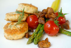 Chicken cutlets with asparagus and tomatoes Stock Photos